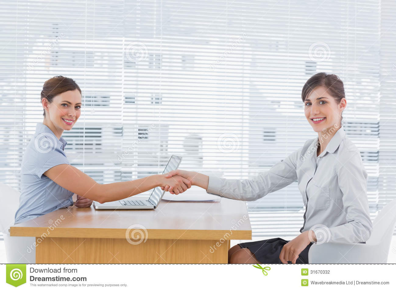 businessw shaking hands interviewee and both smiling at businessw shaking hands interviewee and both smiling at
