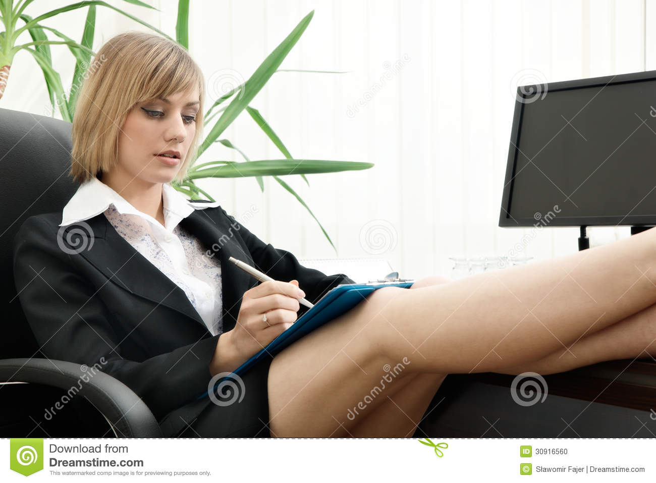 Businesswoman Sitting With Feet Up On Desk Stock Photo