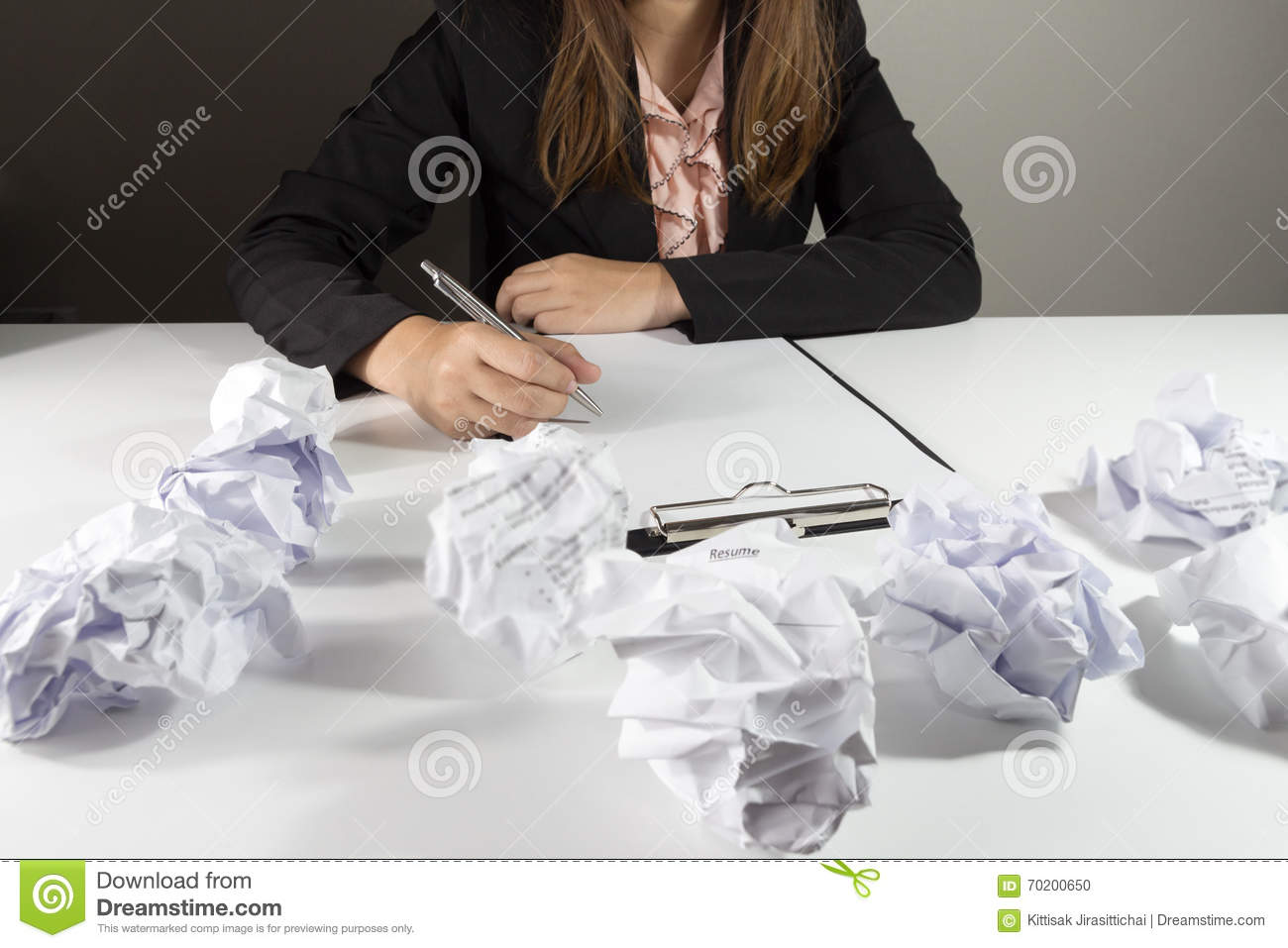 businesswoman sitting at her desk with mistake resume stock photo
