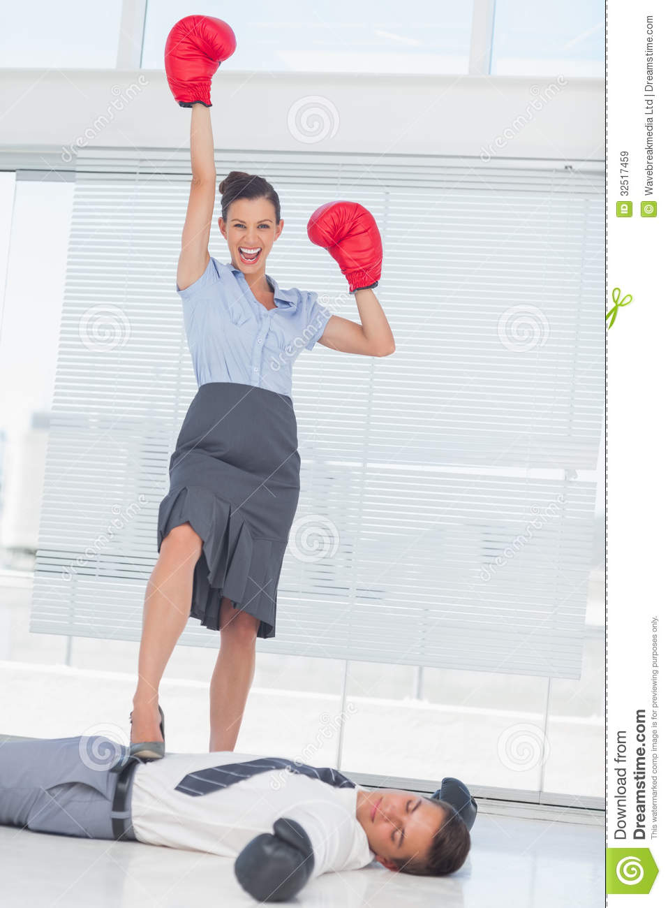 Businesswoman Standing On Defeated Businessman Wearing