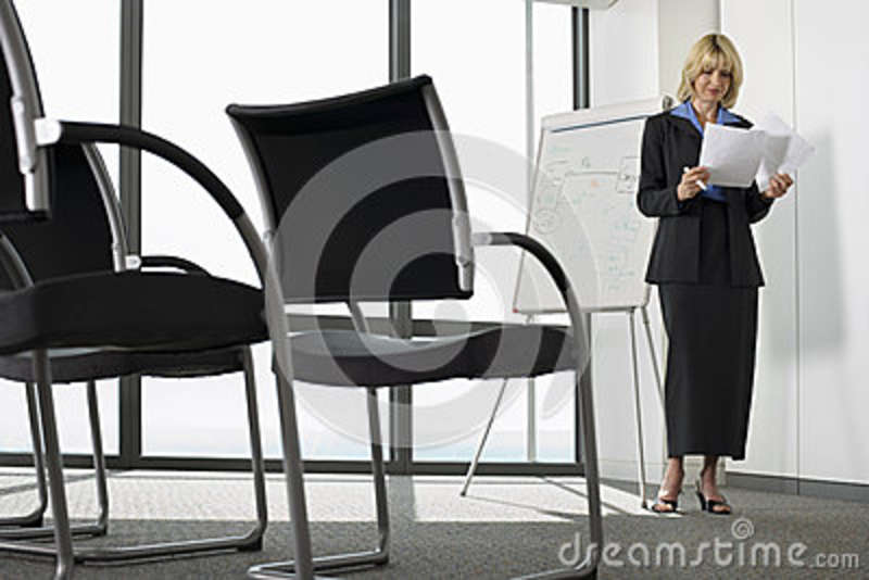 Businesswoman standing beside whiteboard in empty conference room, preparing for presentation