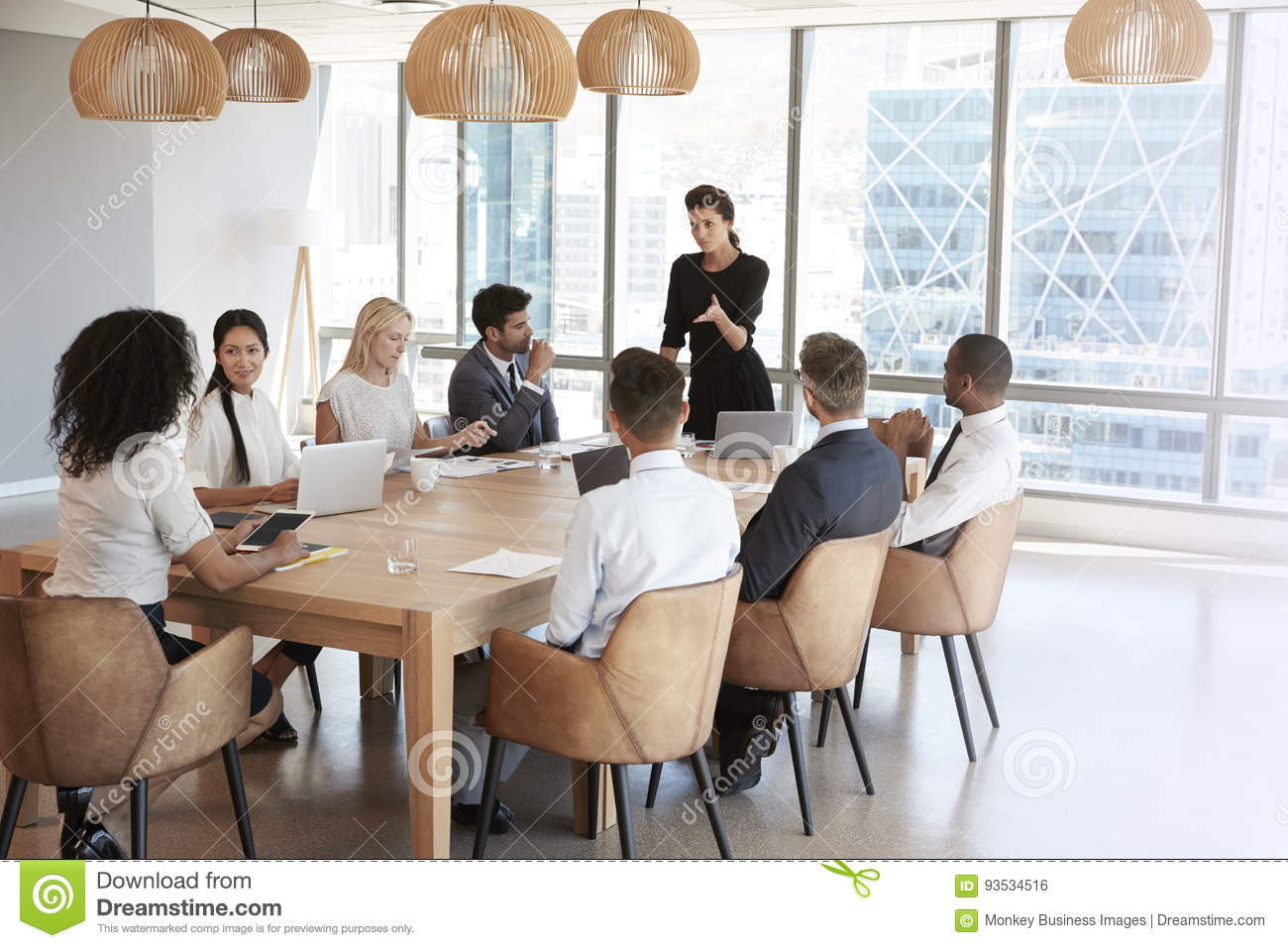 Magnificent Businesswoman Stands To Address Meeting Around Board Table Beutiful Home Inspiration Ommitmahrainfo