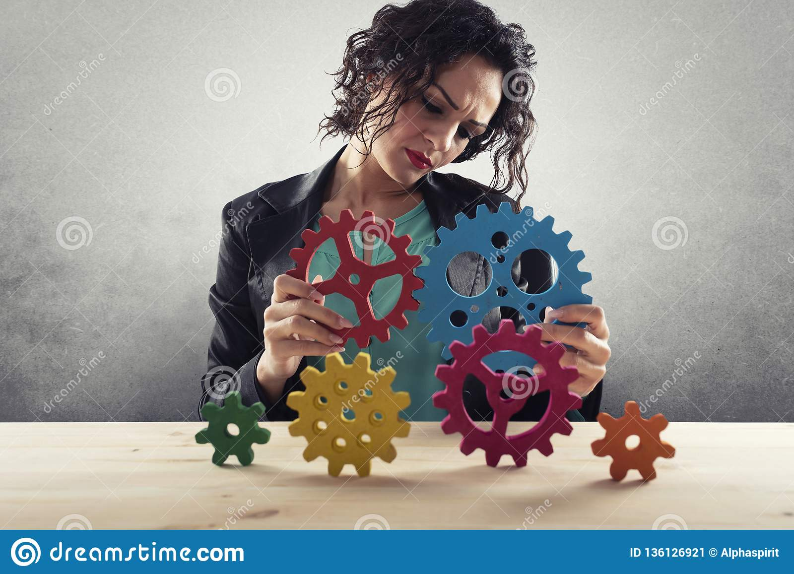 Businesswoman tries to connect gears pieces. Concept of Teamwork, partnership and integration
