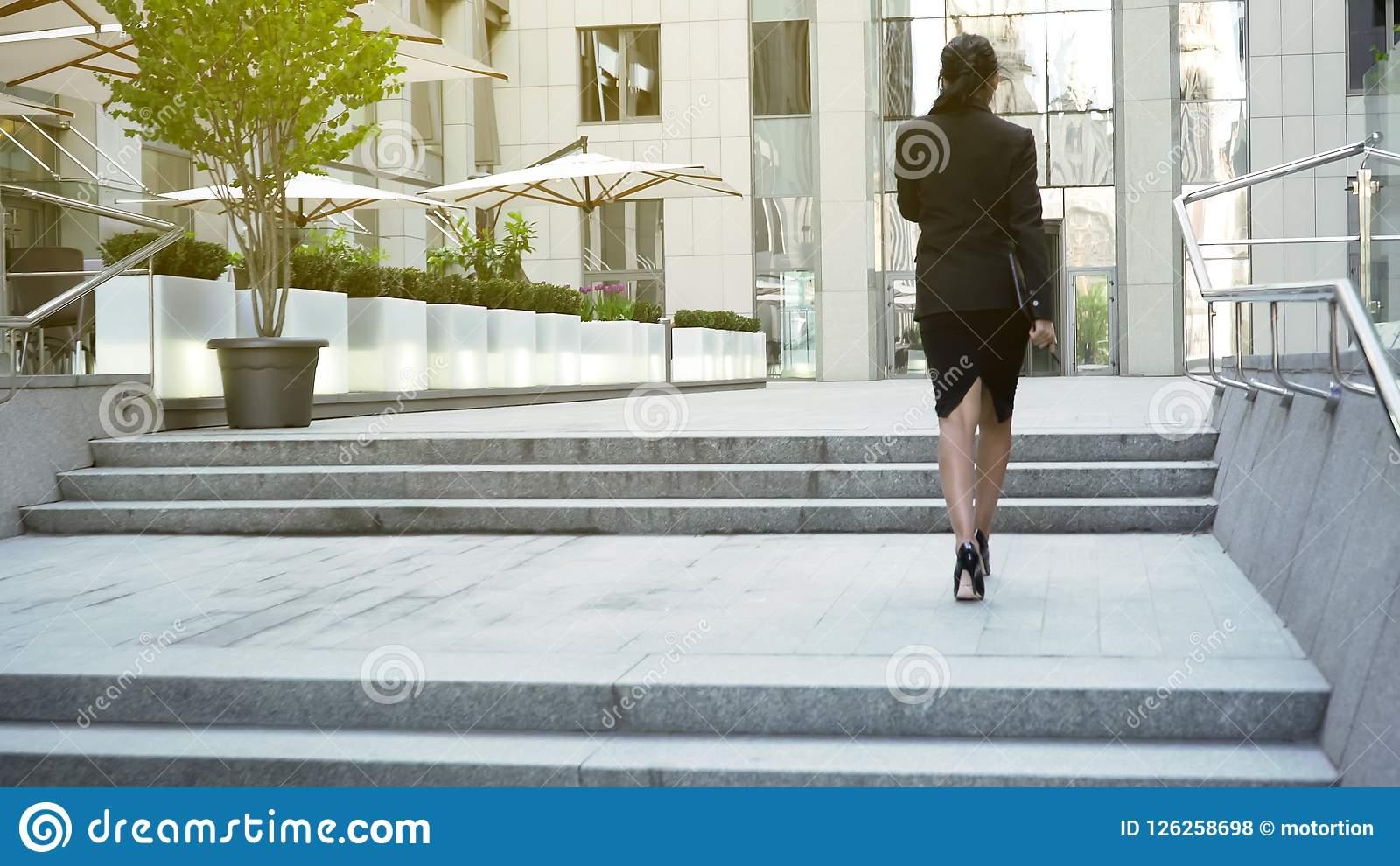 Businesswoman walking upstairs to building, moving up career ladder, success