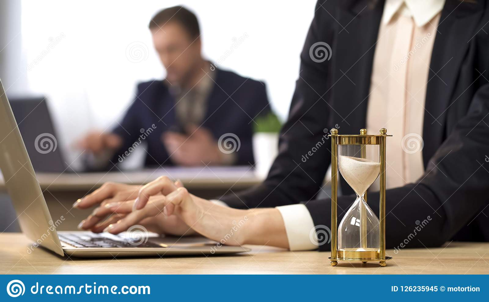 Businesswoman working on computer, hourglass trickling, outcome anticipation