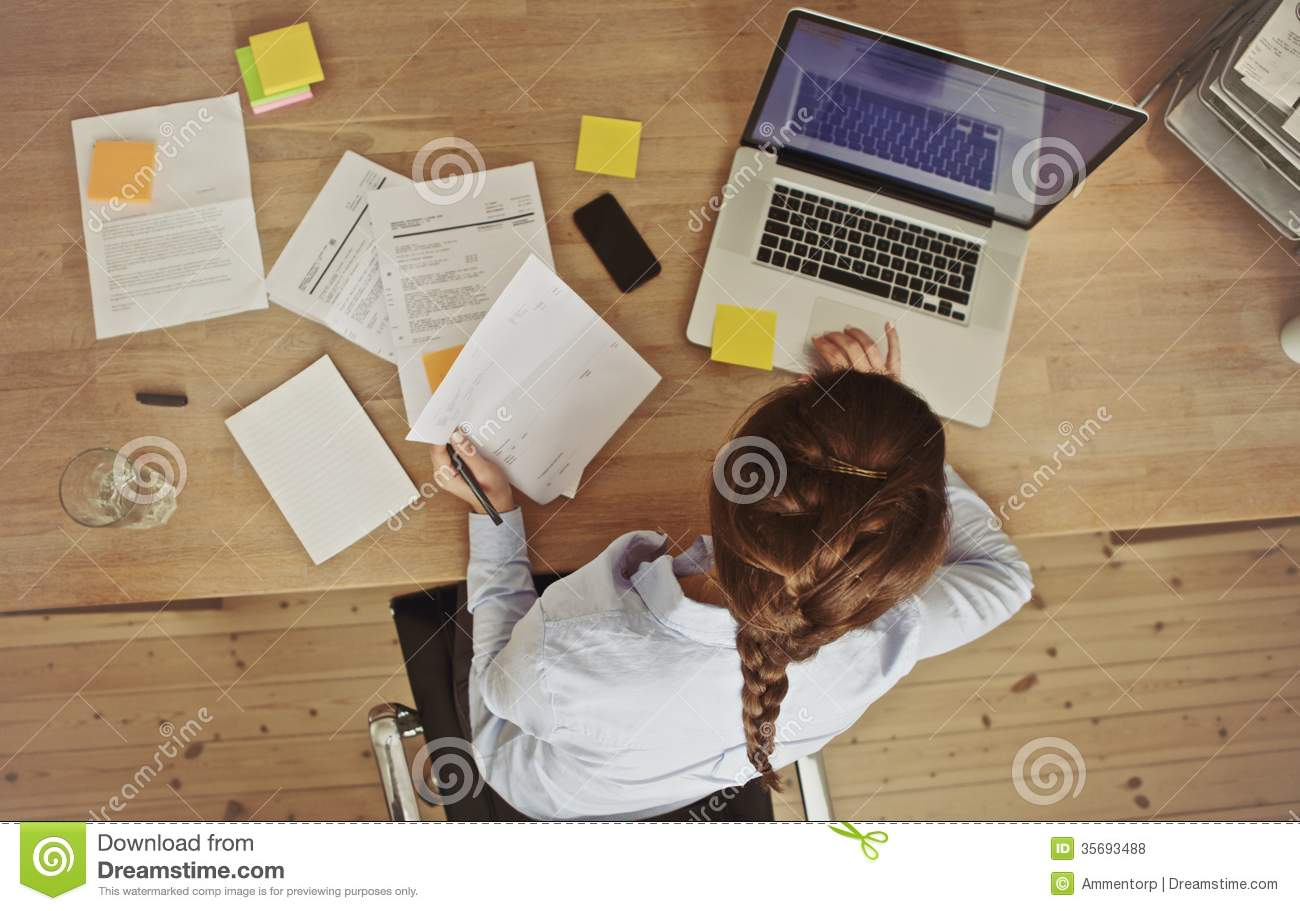 Businesswoman working at her office desk with documents and laptop