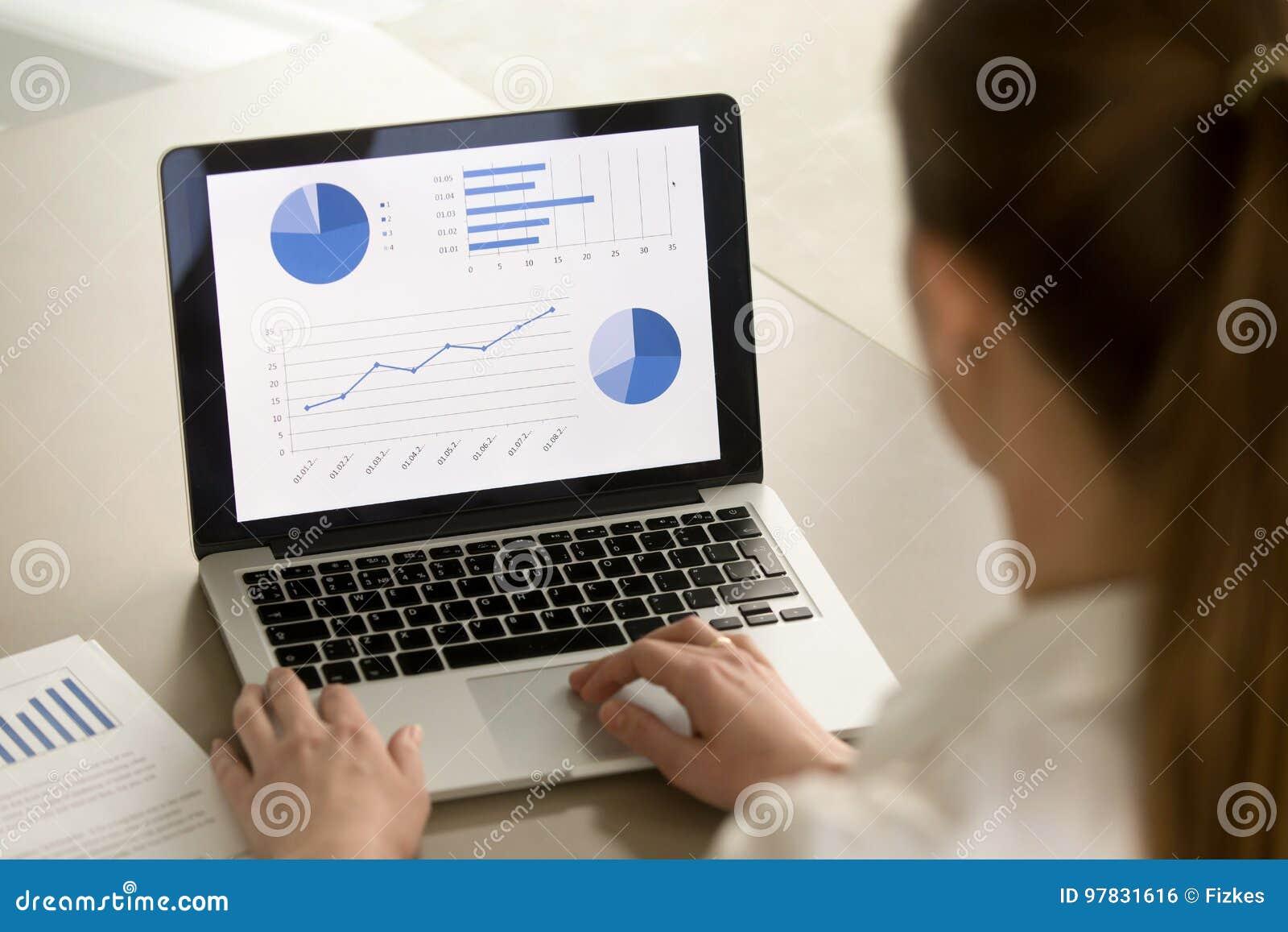 Businesswoman working on laptop, analyzing statistics, software