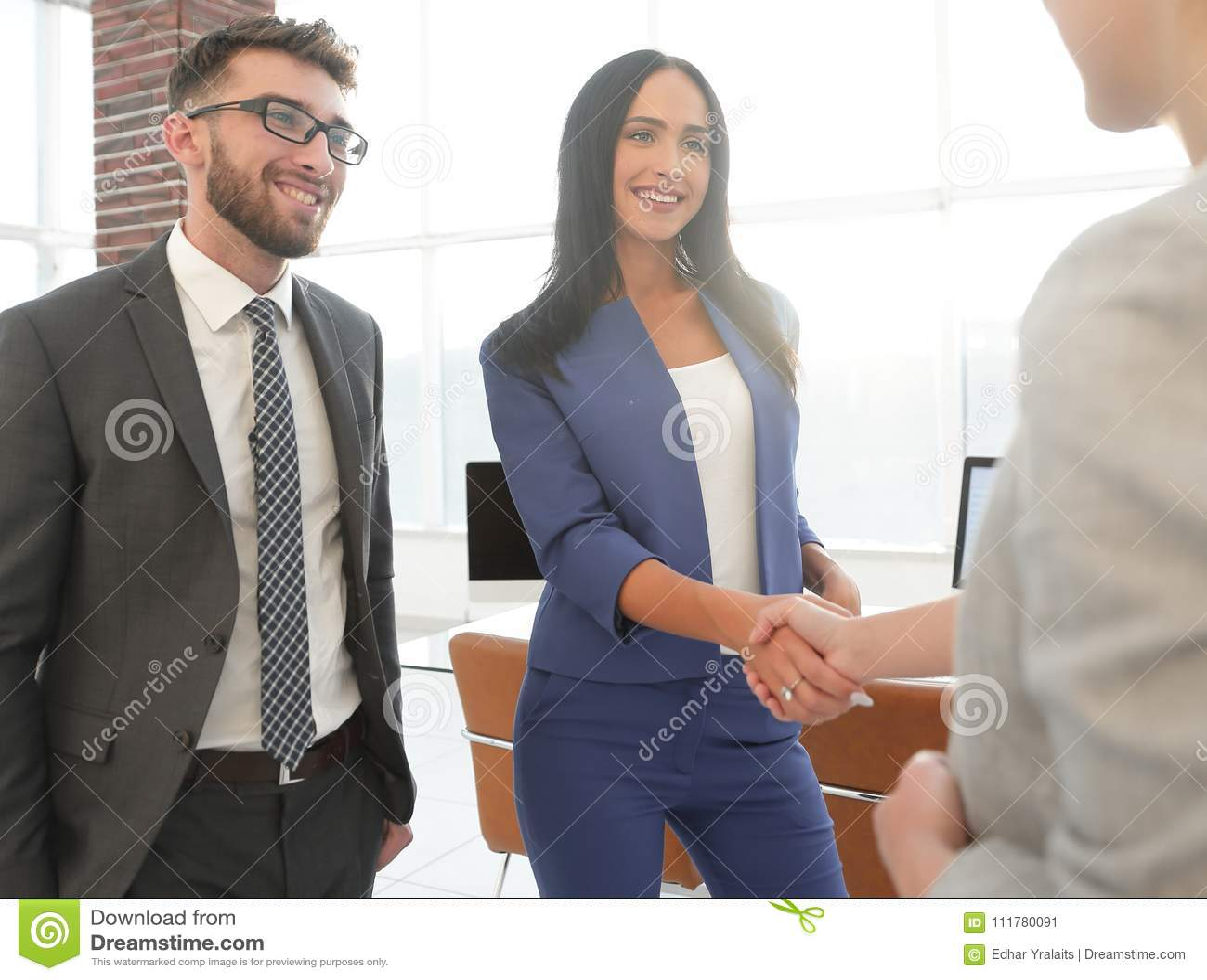 Two beautiful businesswomen handshaking in office