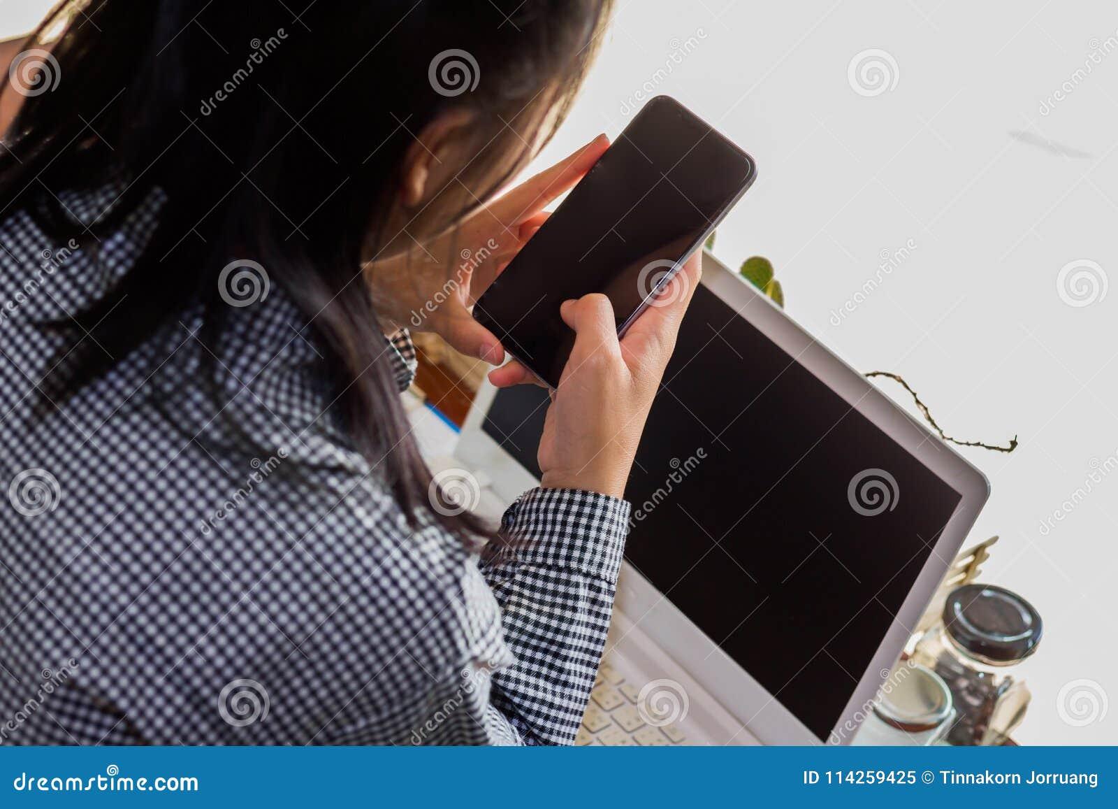 Businesswomen using cellphone working in coffee shop.