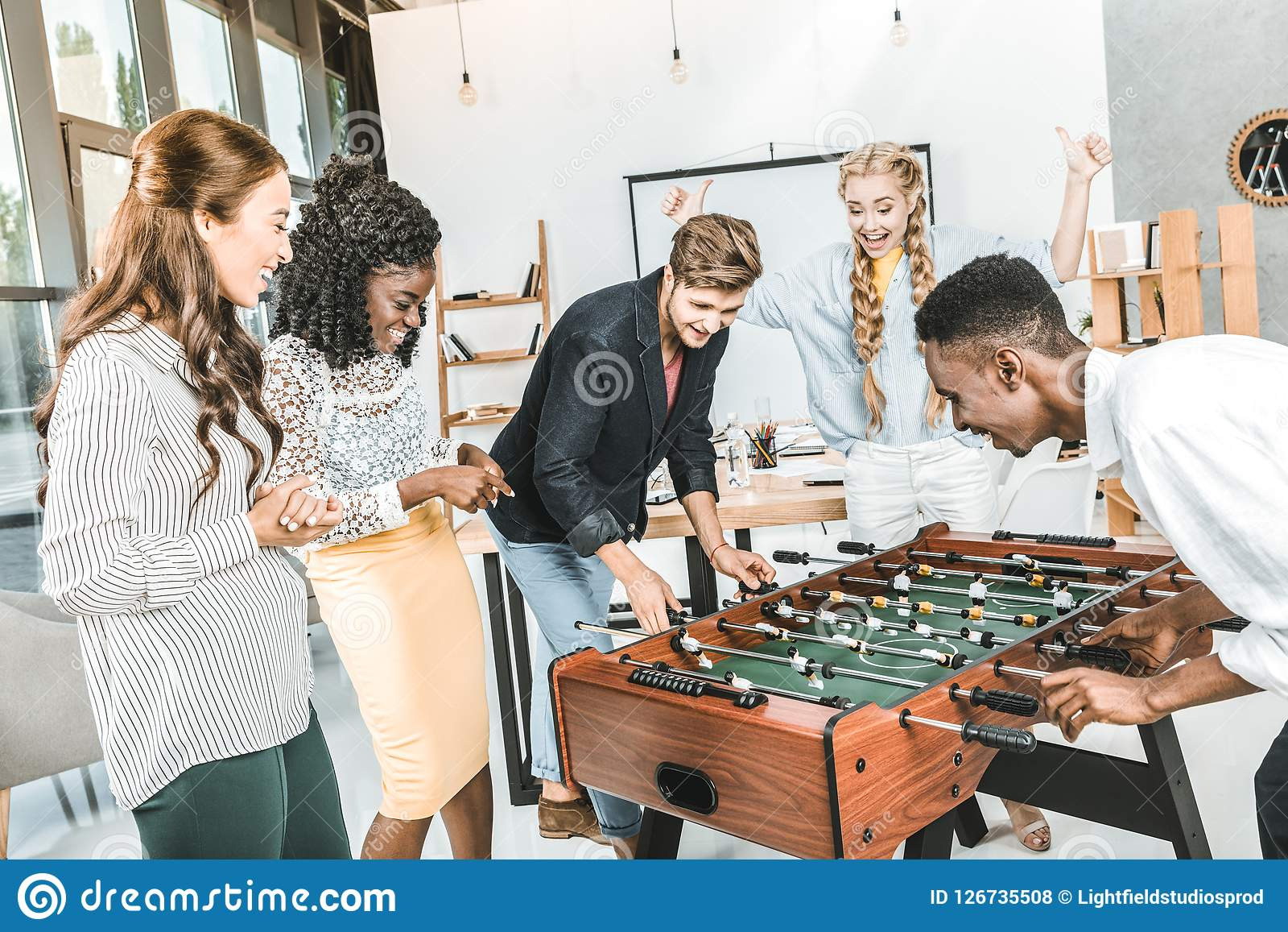 businesswomen watching multicultural colleagues playing table football 32a4f48d52