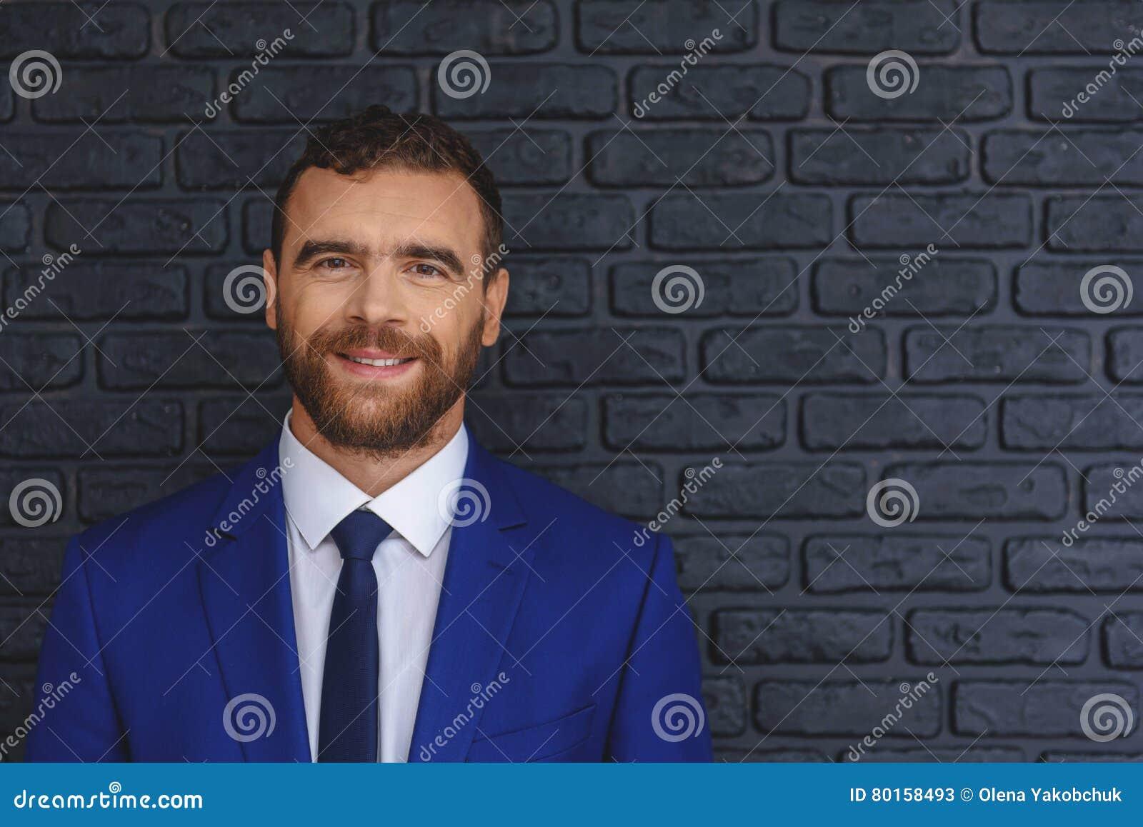 Bussinesman barbu futé sur le fond de briques