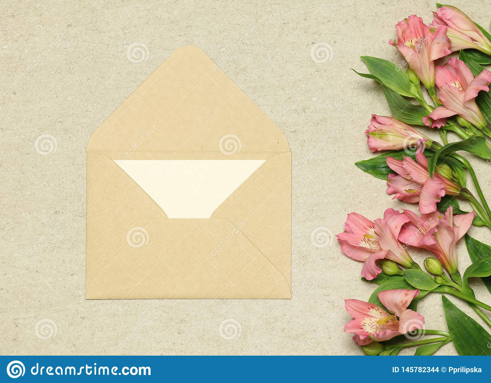 Busta beige del mestiere con carta ed i fiori su fondo di pietra
