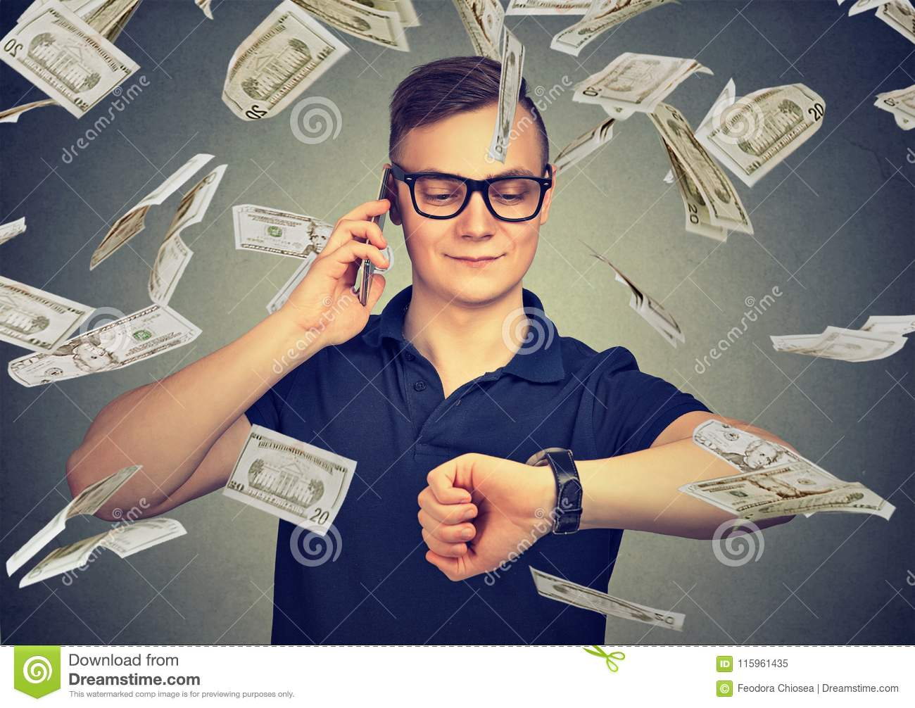 Busy businessman looking at wrist watch, talking on mobile phone under cash rain. Time is money concept