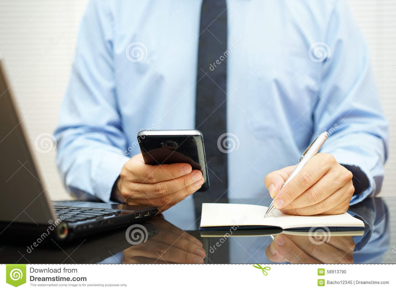 Photo: Busy Businessman At Office Desk Is Using Smart Mobile Phone Wr. Full resolution  image, nominally Width 1300 Height 957 pixels, image with #9E6D2D.
