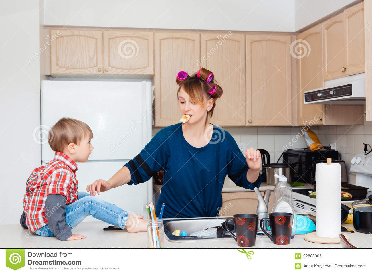 Busy white Caucasian young woman mother housewife with hair-curlers in her hair cooking preparing dinner meal in kitchen