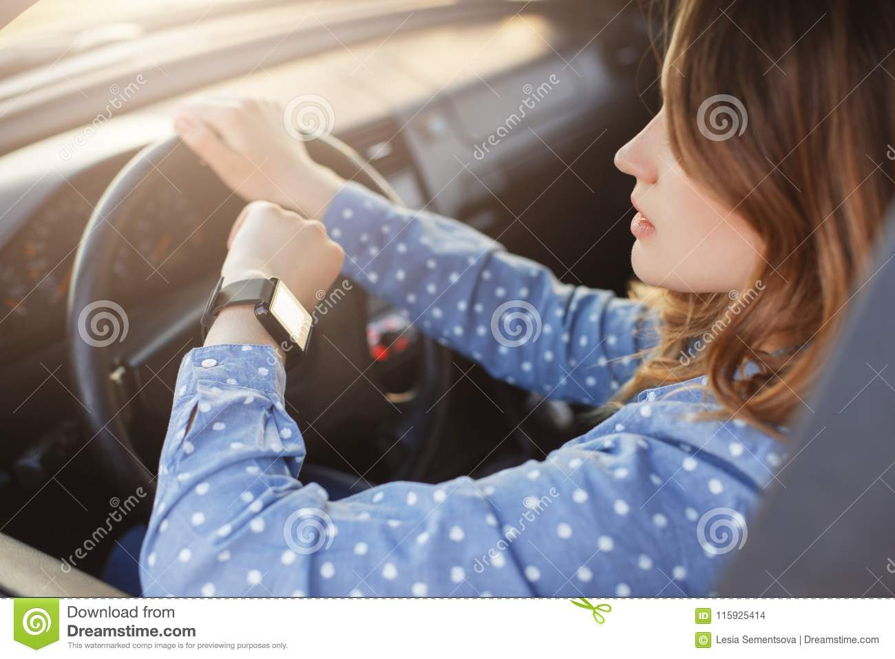 Busy young woman drives car and looks at watch, stuck in traffic jam, hurries to work, being nervous and stressed, feels impatient