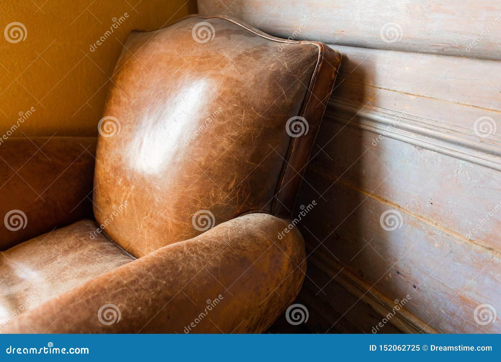 Butaca de cuero del viejo vintage con el fondo de madera