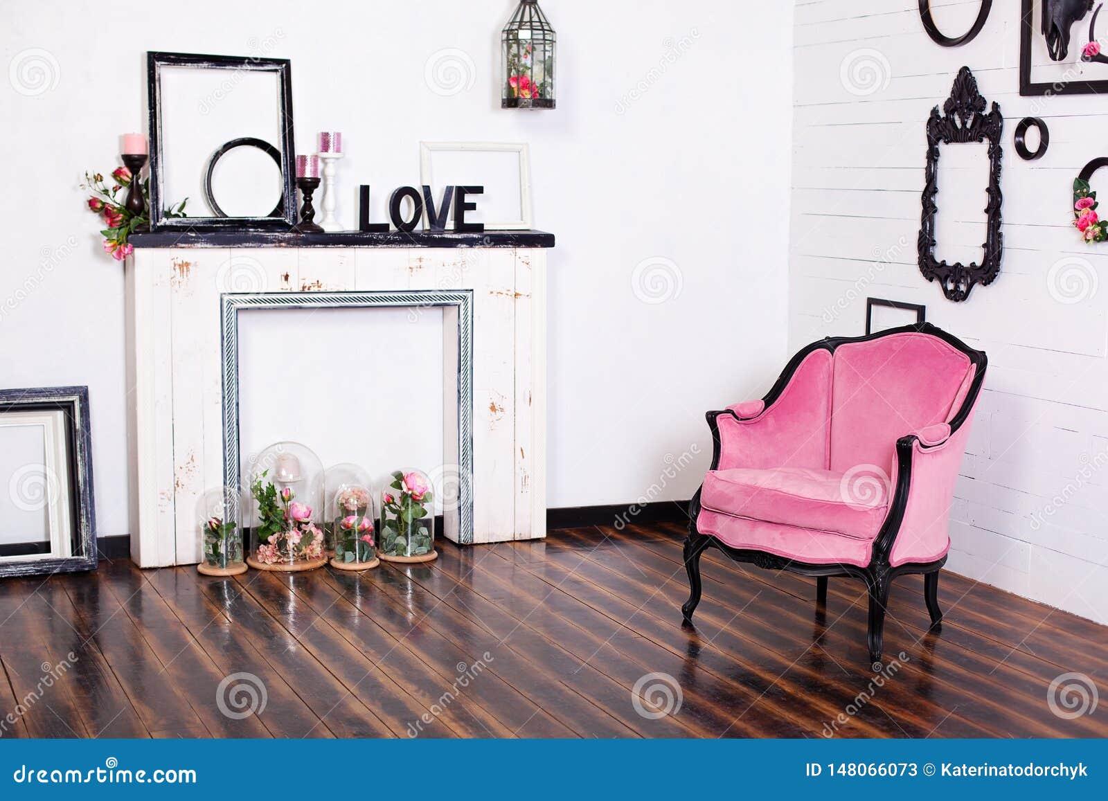 Butaca del velor del vintage, en un cuarto brillante y una chimenea artificial Ático interior con las paredes blancas de madera M