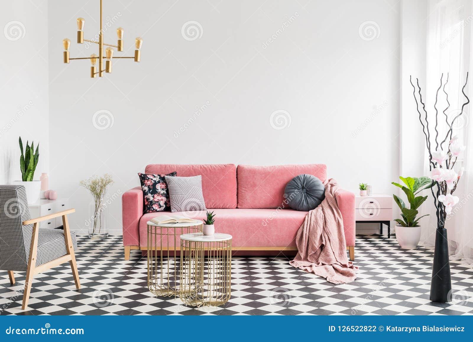 Butaca modelada cerca de las tablas del oro y del sofá rosado en el interior plano blanco con las plantas Foto verdadera