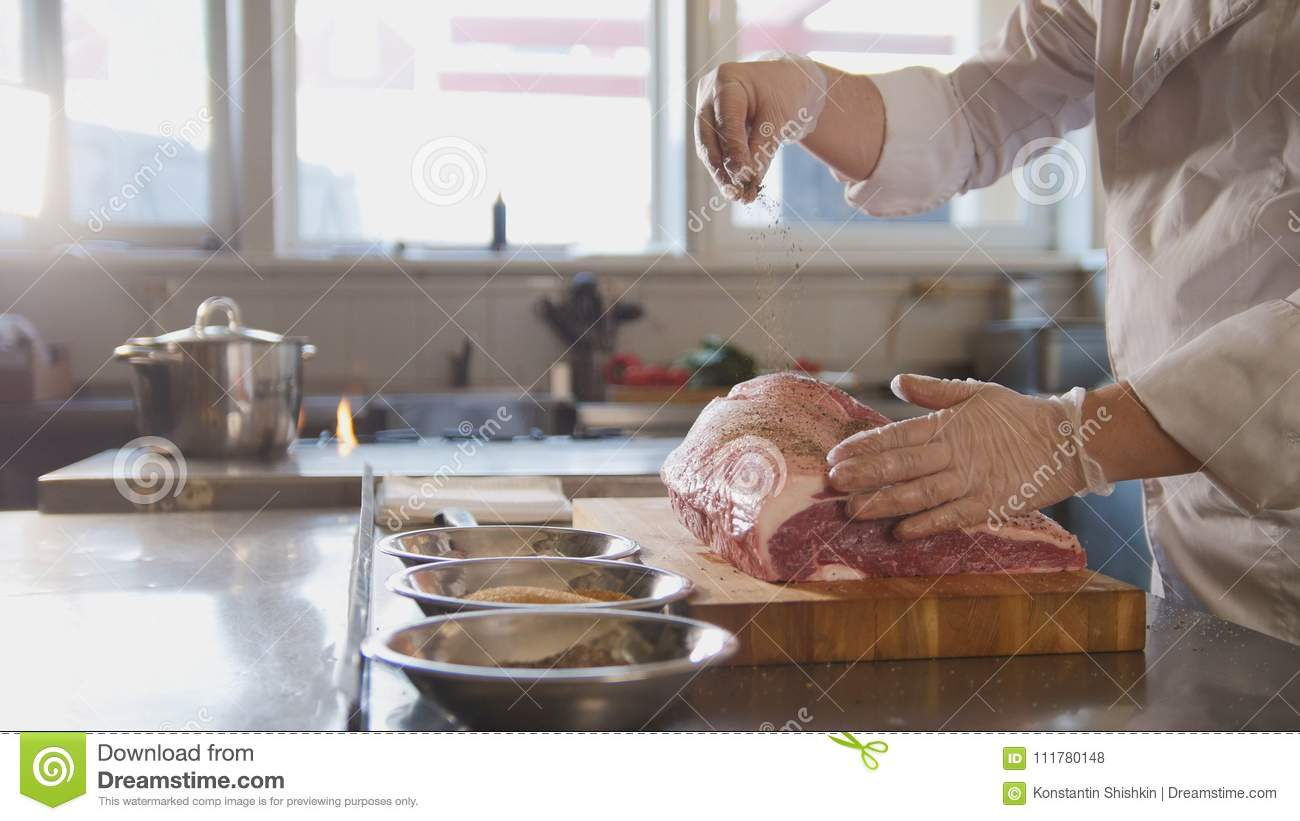 Butcher adding spices into large piece of fresh raw meat lying on a wooden board in a commercial kitchen