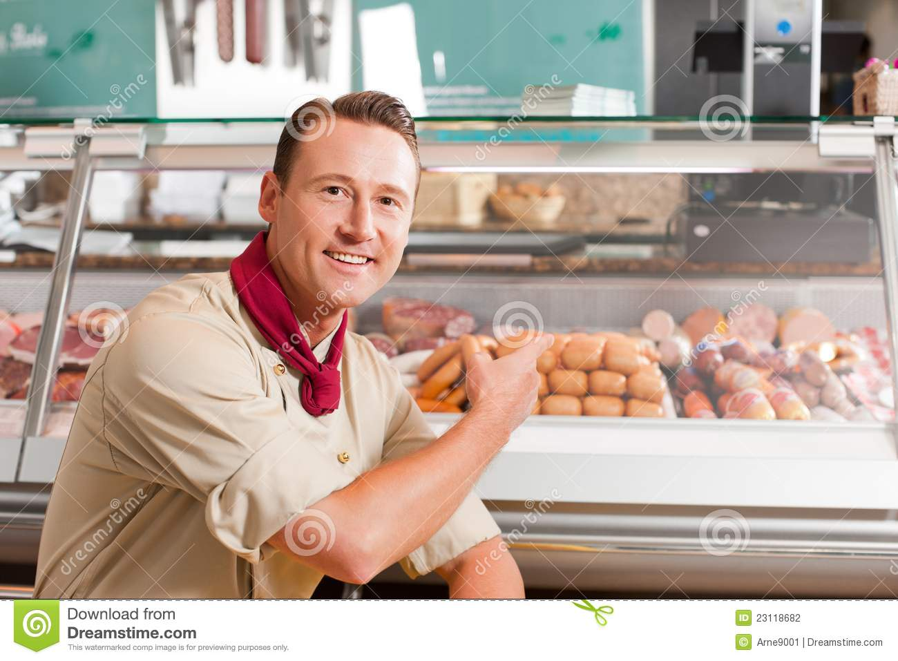 Stock photography butcher pointing at fresh meat for selling