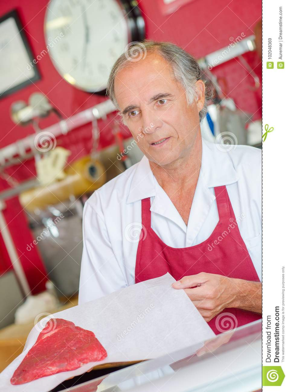 Butcher presenting cut beef to customer