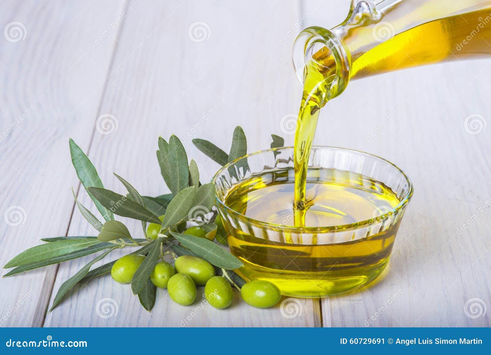 Buteljera hällande jungfrulig extra olivolja i en bunke