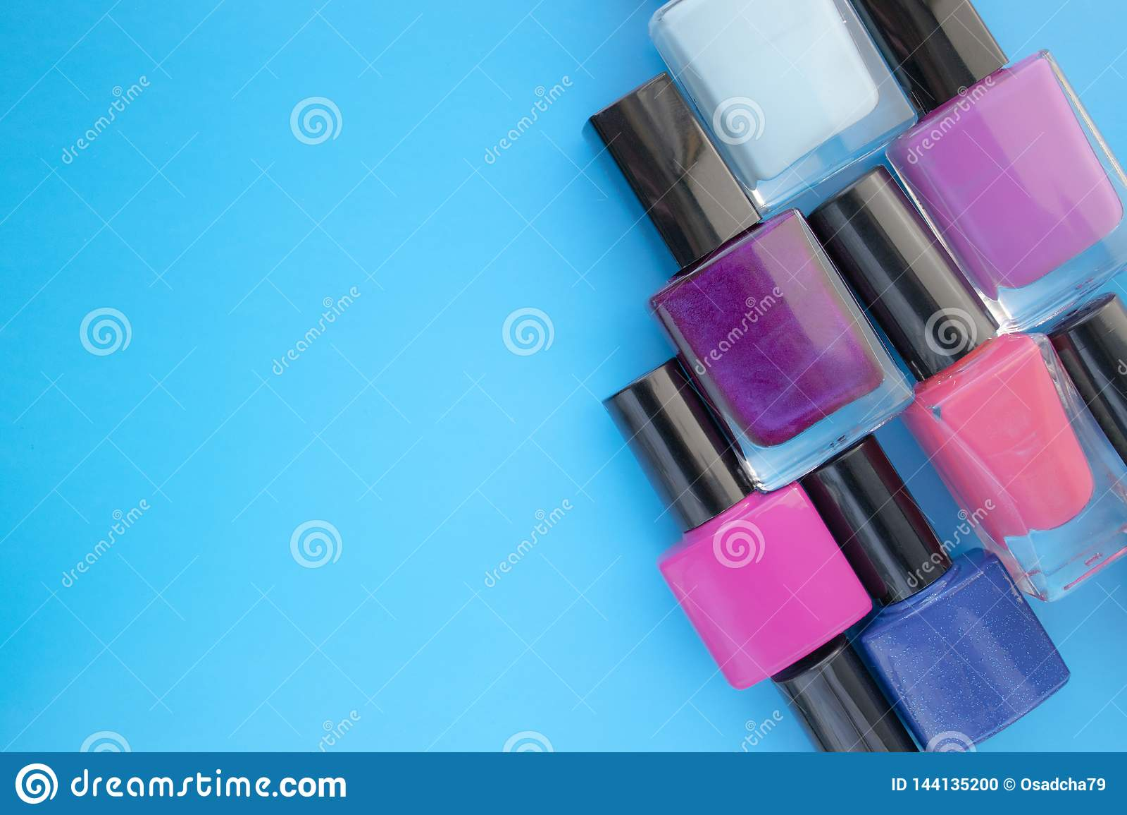 Butelkę lakieru do paznokci Grupa jaskrawi manicure na błękitnym tle Z pustą przestrzenią na lewicie