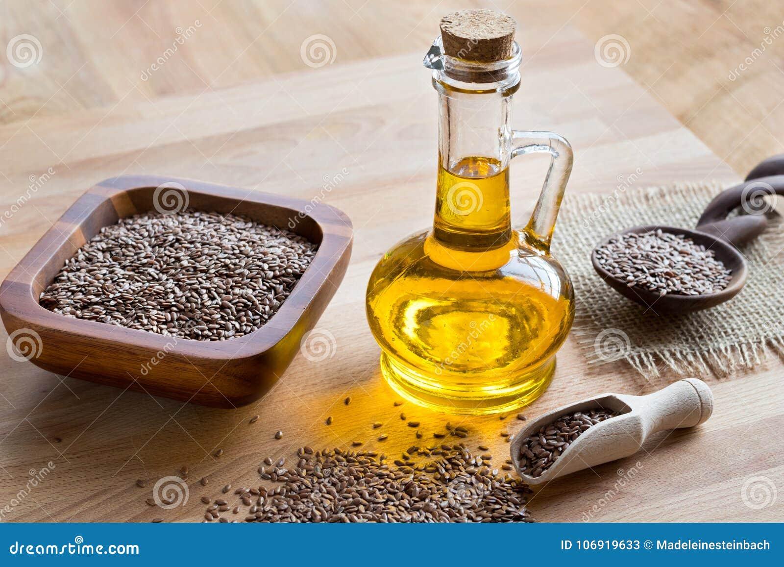 Butelka flaxseed olej z lnów ziarnami w tle,