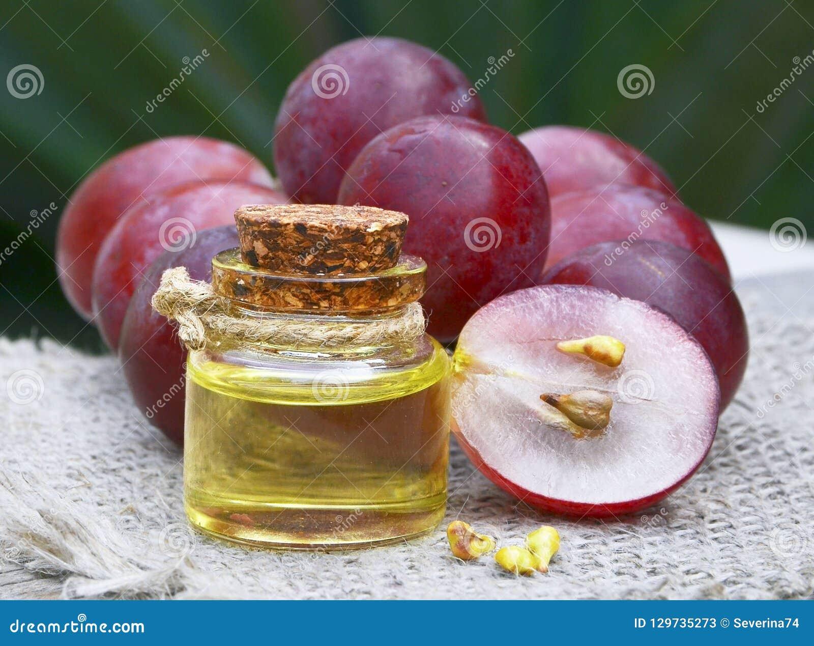 Butelka organicznie gronowy nasieniodajny olej dla i świeże dojrzałe winogrono jagody na starym drewnianym stole zdroju i bodycar