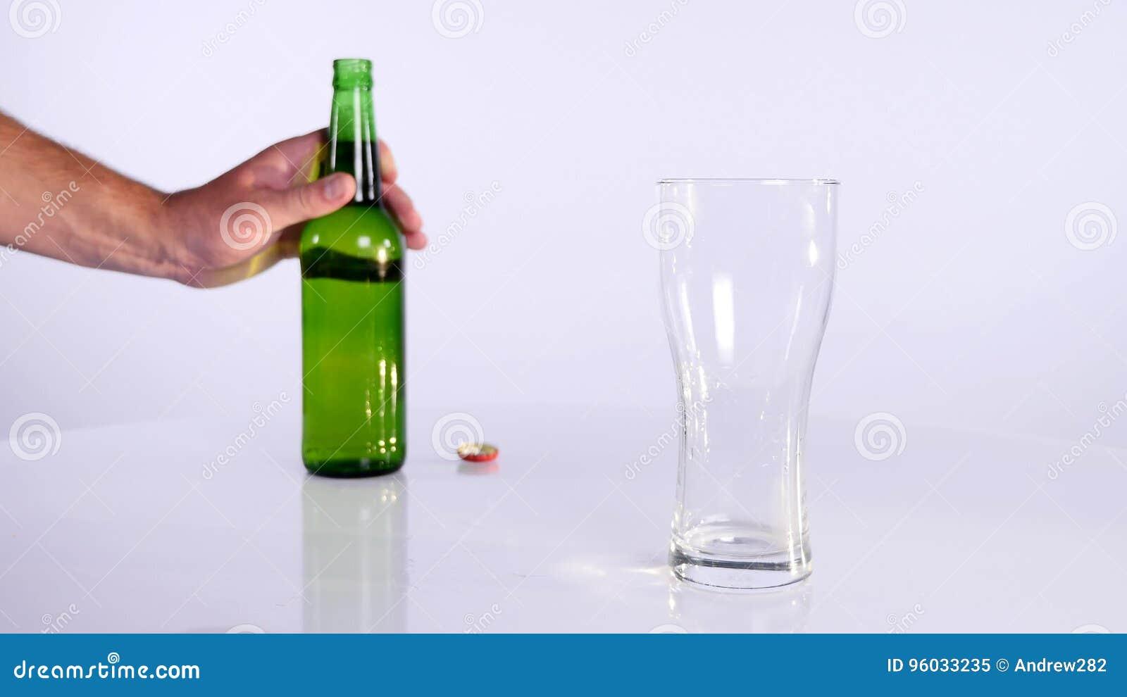 Butelka piwo nalewa w filiżankę na białym tle