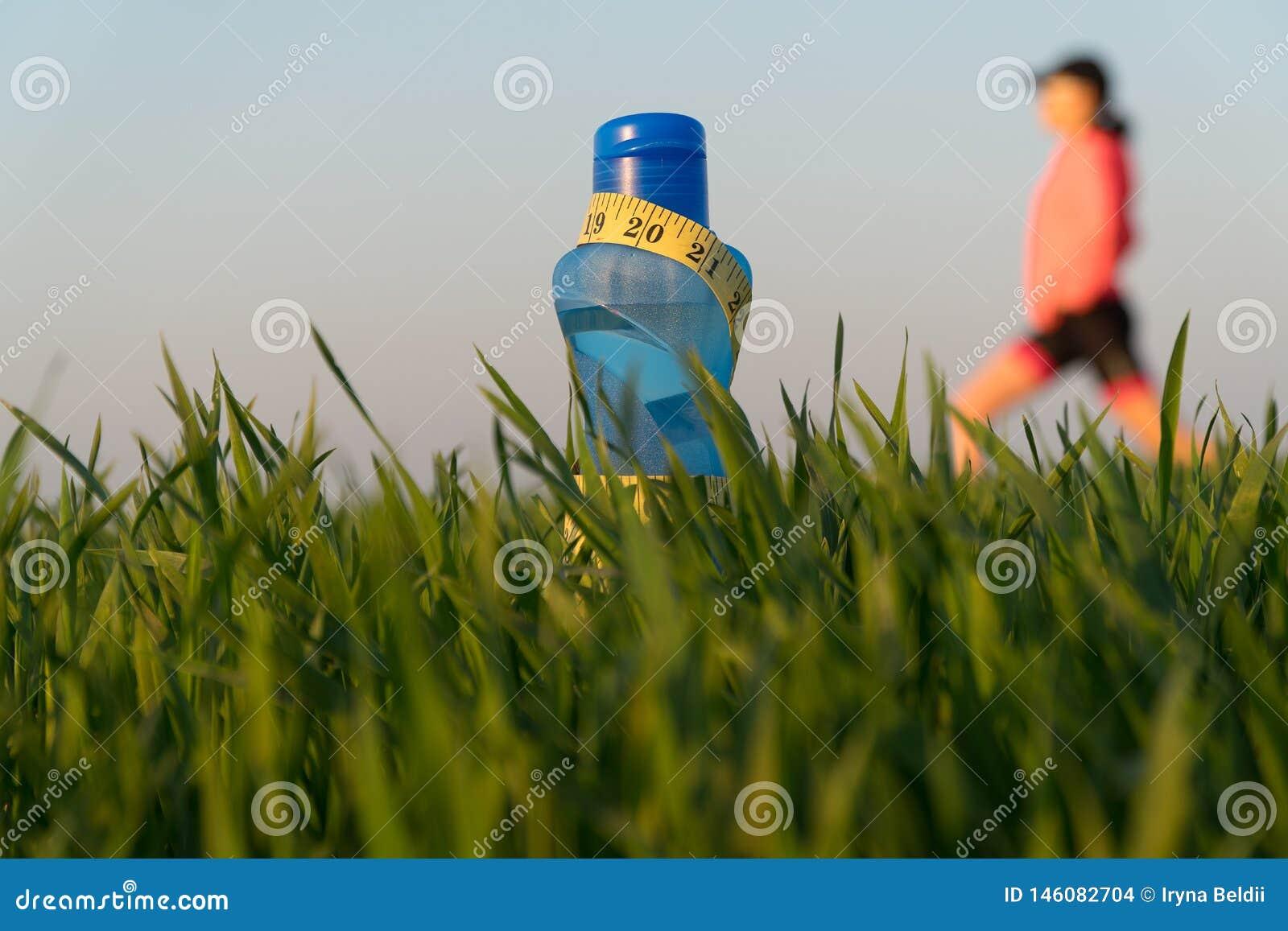 Butelka sport woda butelka stojaki na trawie Sporty styl ?ycia odosobniona straty miara p??postaci ci??aru bia?ej kobiety
