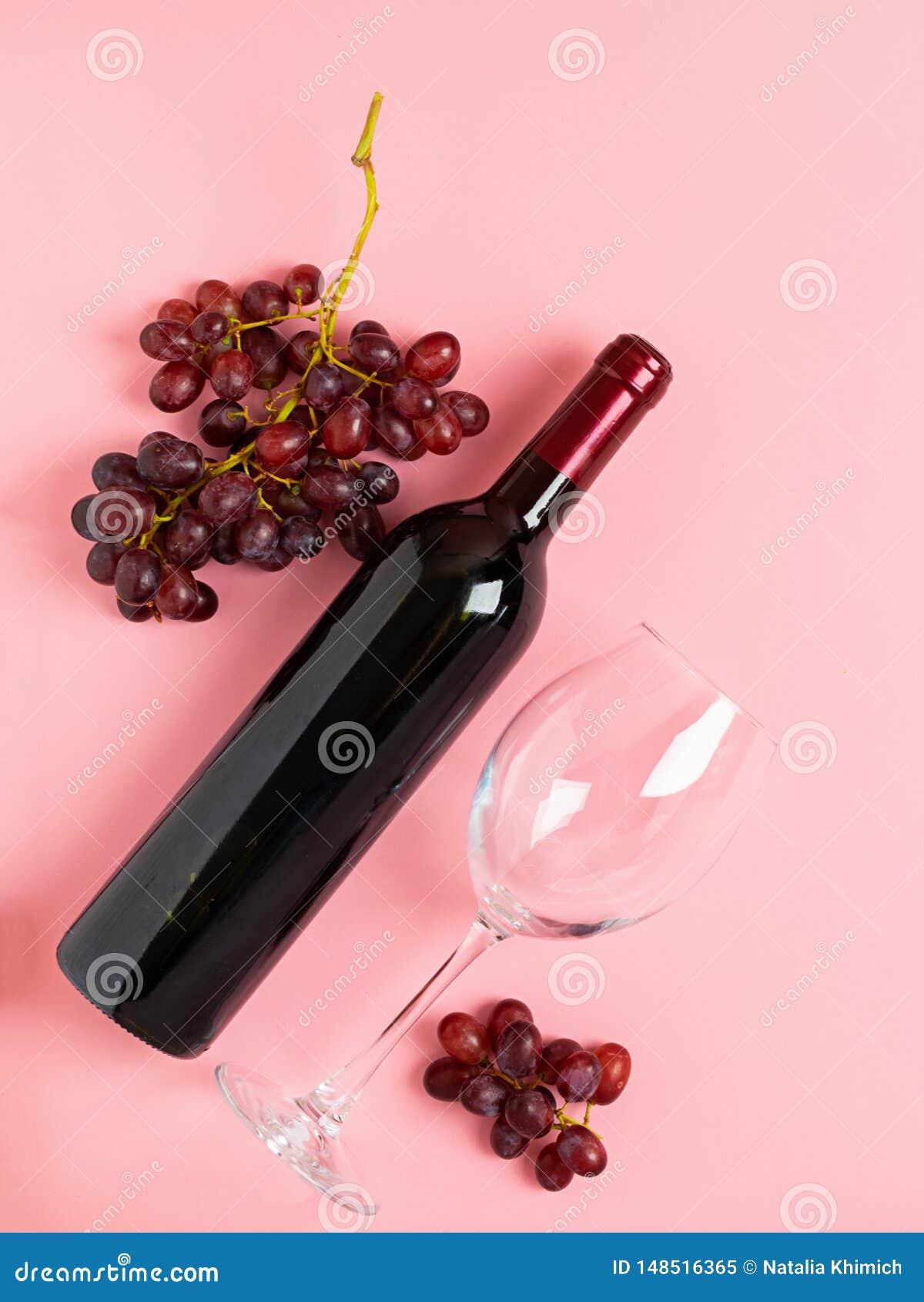Butelka wino pusty szk?o wi?zka winogrona na delikatnym r??owym tle minimalista Odg?rny widok