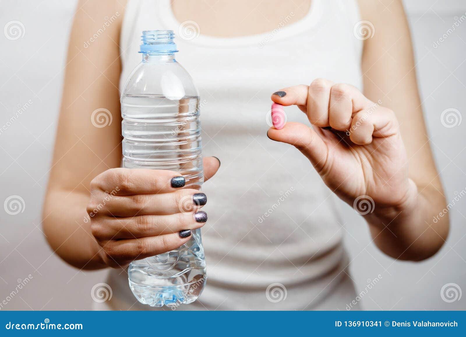 Butelka woda w kobiety ręki pastylce w ręce, witaminy z wodą