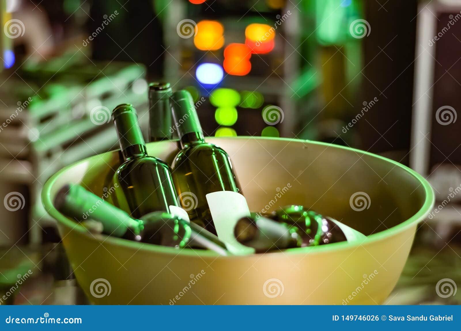 Butelki nieotwarte w stal nierdzewna złotym żelaznym pucharze przy przyjęciem wino - wydarzenie na defocused zielonego światła tl