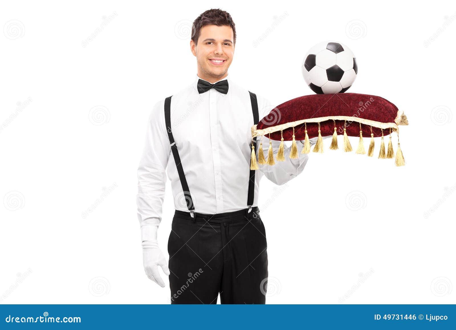 Butler che tiene un cuscino rosso con calcio su