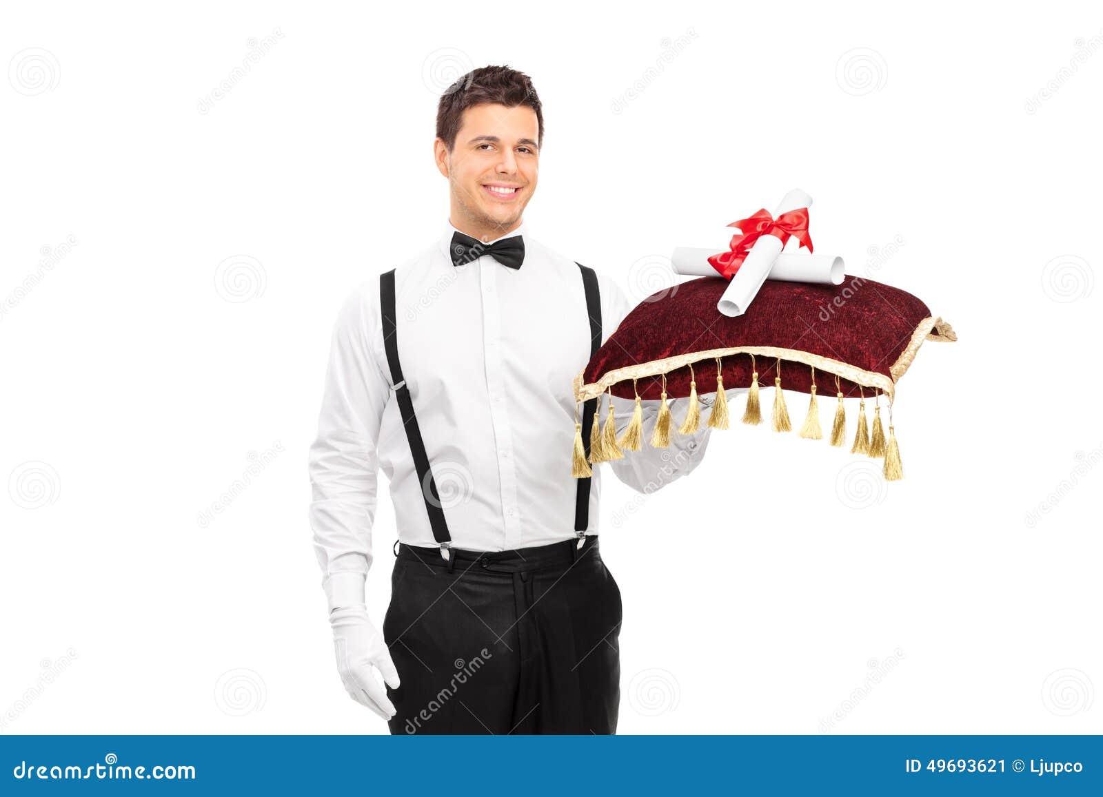 Butler che tiene un cuscino rosso con due diplomi dell università