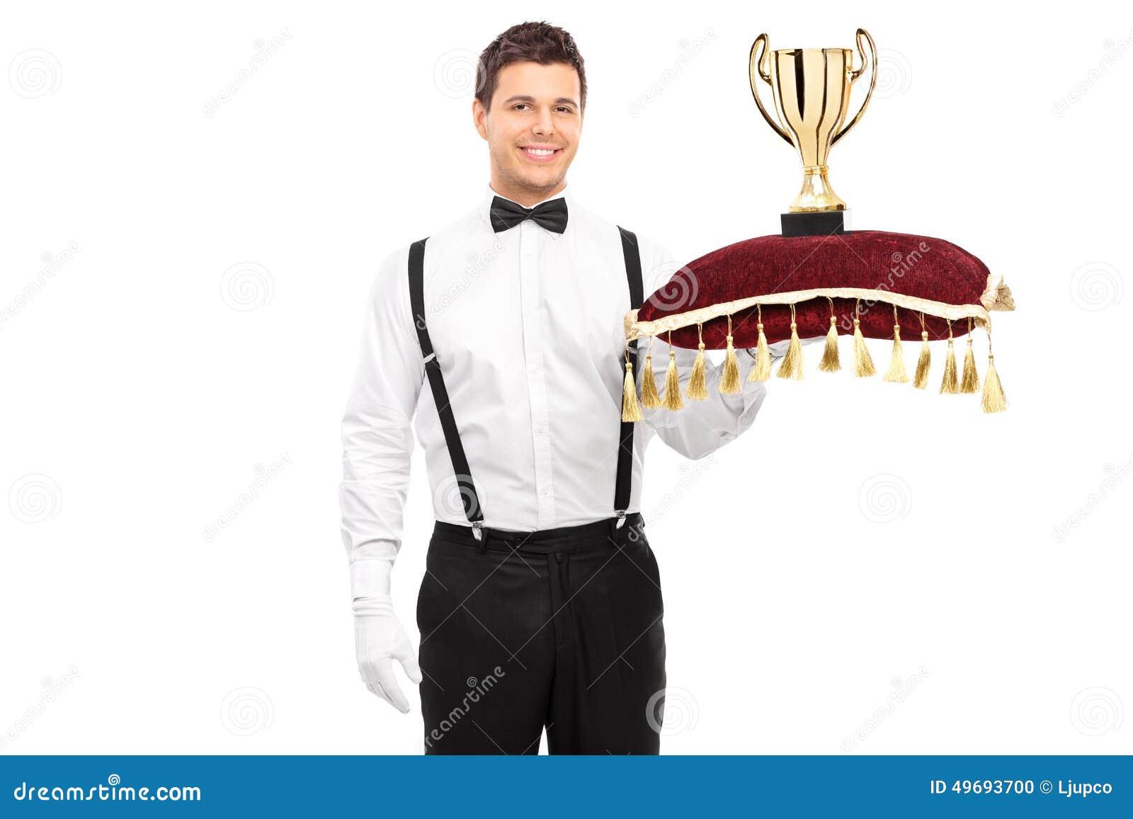 Butler che tiene un trofeo sul cuscino rosso