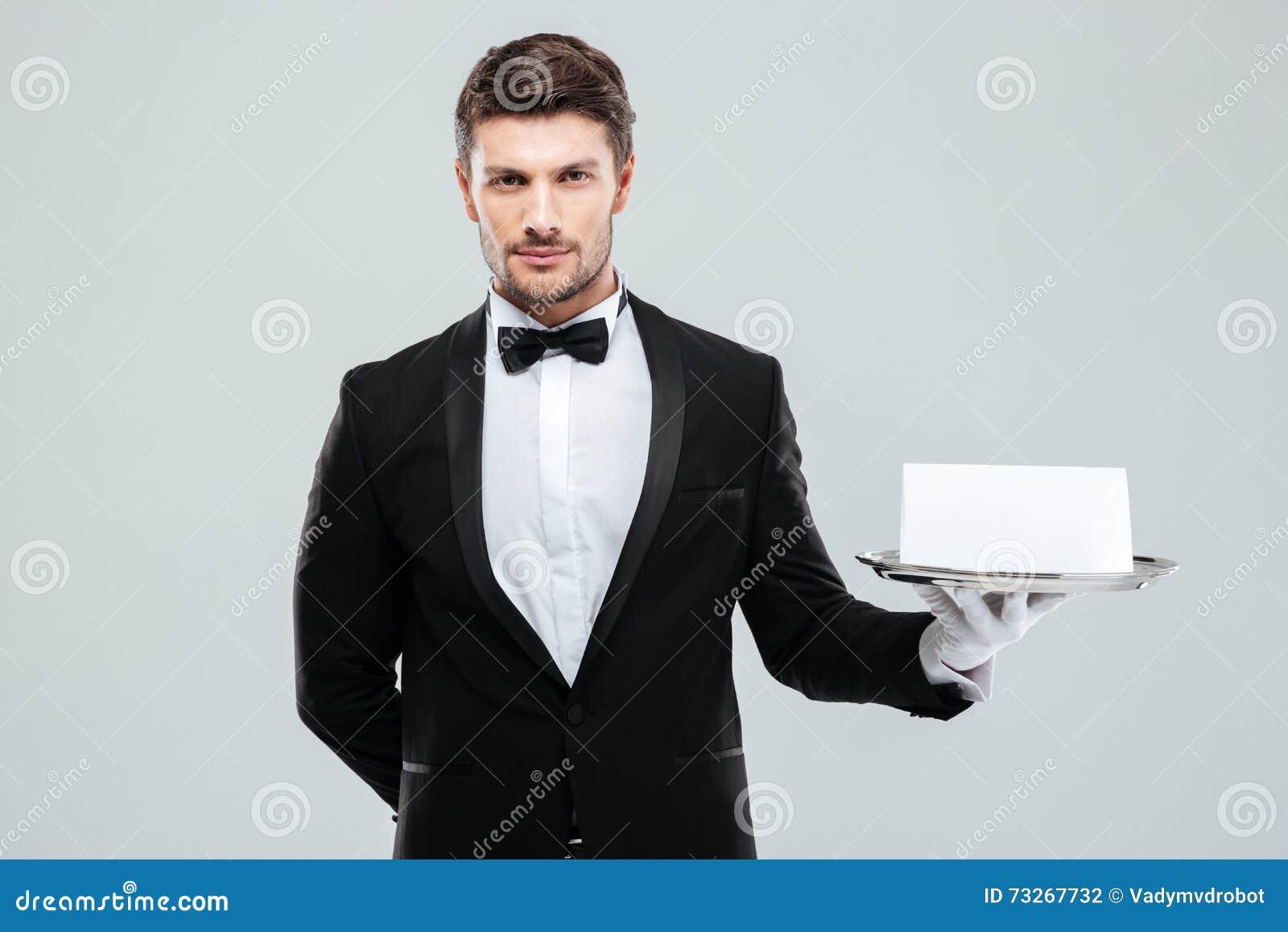 Butler dans le smoking et gants tenant le plateau avec la carte vierge