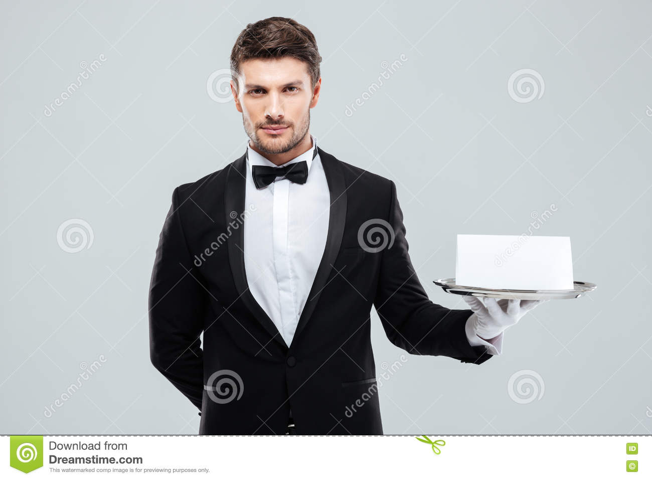 Butler in tuxedo and gloves holding tray with blank card