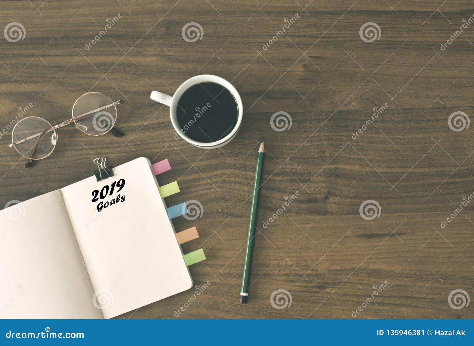 2019 buts énumèrent avec le carnet, tasse de café plus de sur le fond en bois