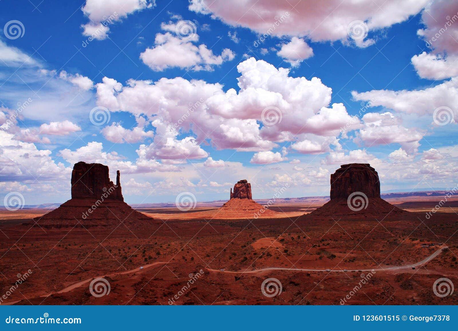 Buttefelsformationen mit Schotterweg, Schatten und flaumigen Wolken im Monument-Tal, Arizona