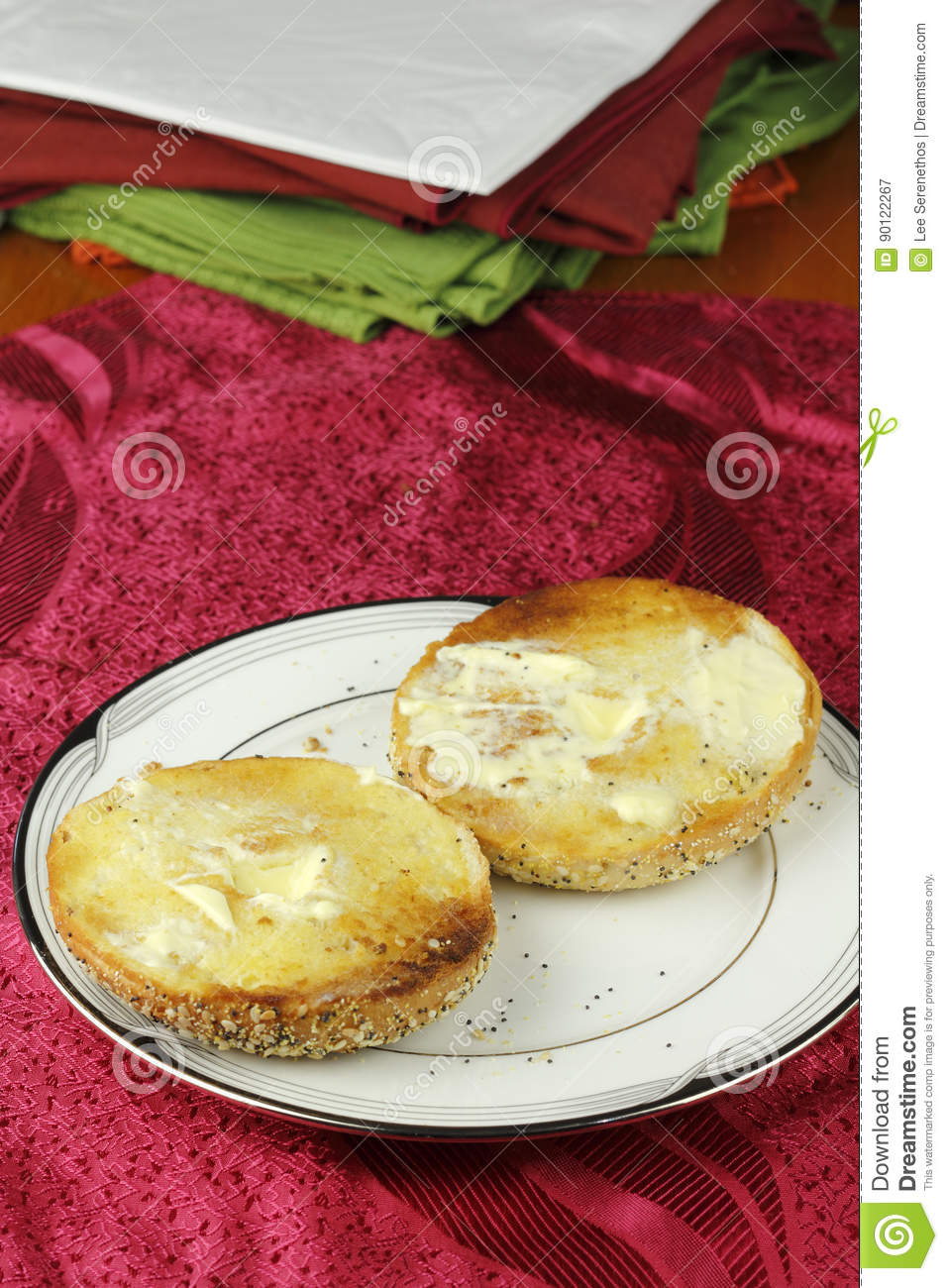 Buttered Everything Bagel on a Plate over a Placemat