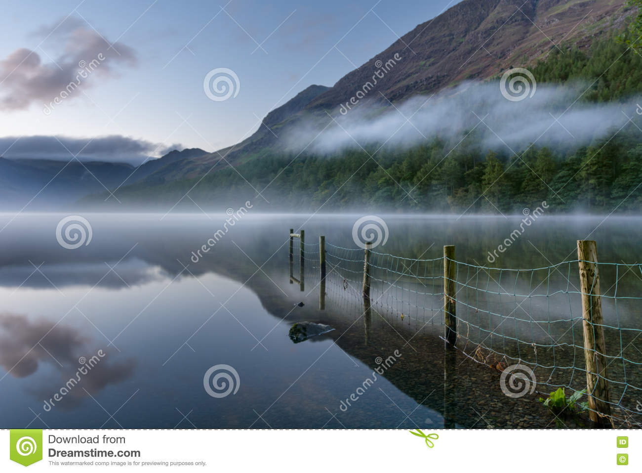 Buttermere Lake At Dawn With Mist And Reflections.