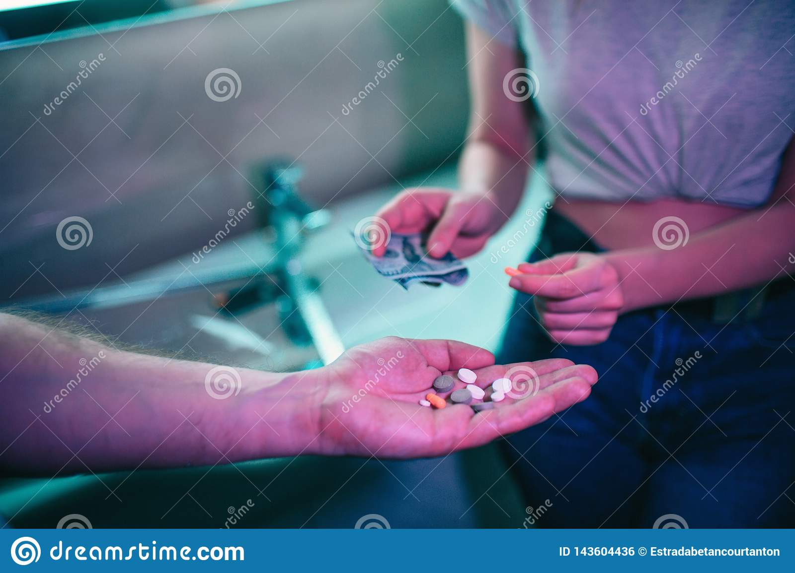 Buying drugs. Drug trafficking and sale. Hand of drug addict with money buying drugs from drug dealer in night club