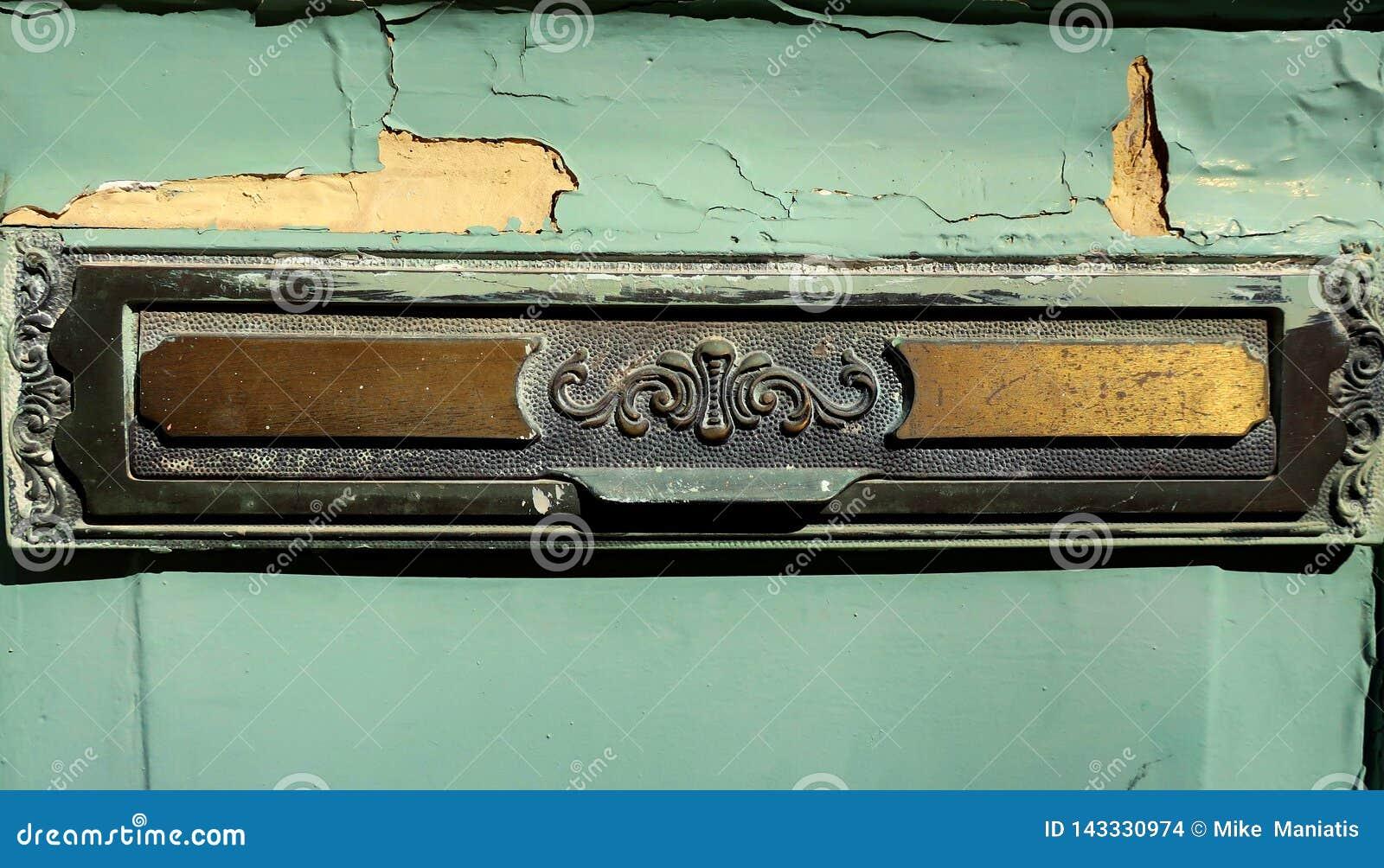 Buzón de cobre amarillo viejo del correo en puerta principal
