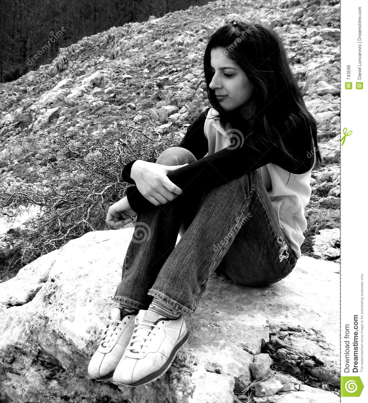 Little white girl sitting on rock sur que