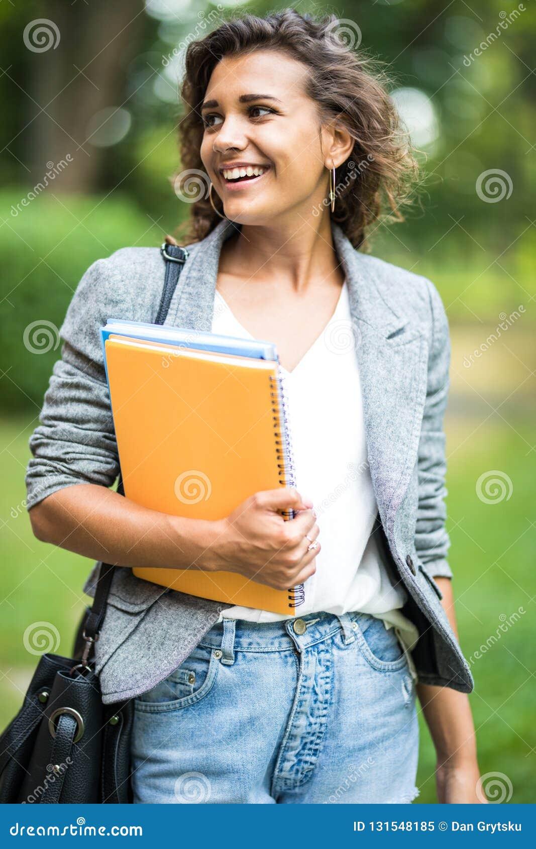 Byczy beztroski dziewczyny obejmowanie rezerwuje w parku podczas gdy przychodzący do domu po klas w uniwersytecie Rozochocony atr
