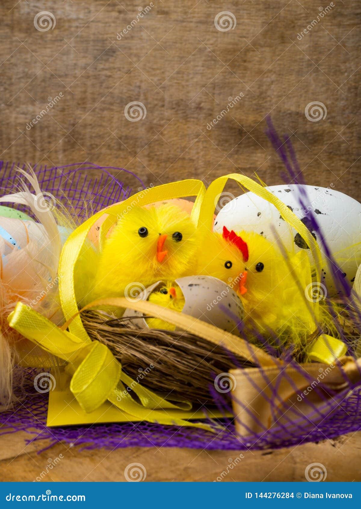Bygga bo dekorativ sammansättning för påsken med gula hönor, färgägg och färgrika fjädrar på träbräde