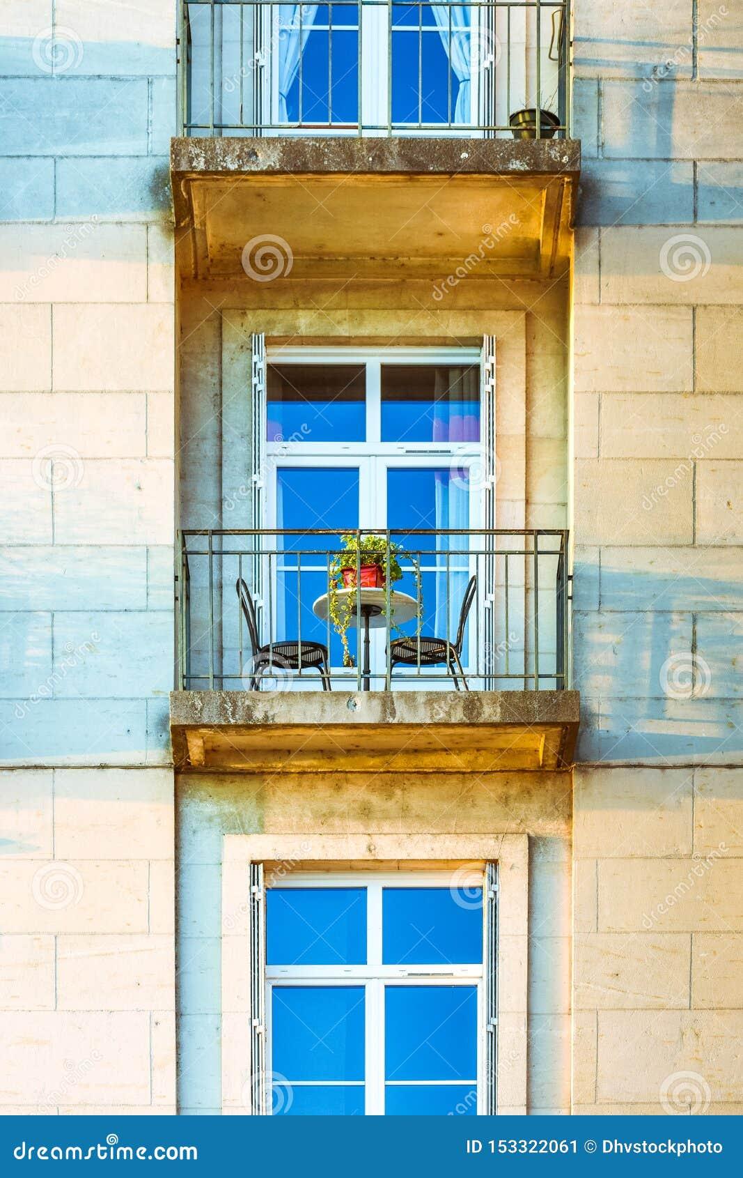Byggande fasad med fönster och en balkong på solnedgången Tabell och stol för två personer